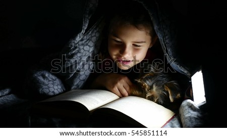 teen child reading girl reads book dog at night with flashlight lying under a blanket
