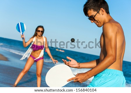 Teen couple in swim wear playing smash ball beach tennis outdoors.