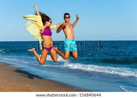 teen couple jumping high on sunny beach. - stock photo