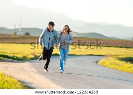 Teen couple running along road in countryside. - stock photo