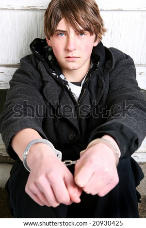 teen crime - teenager with remorseful look in handcuffs against wall - stock photo
