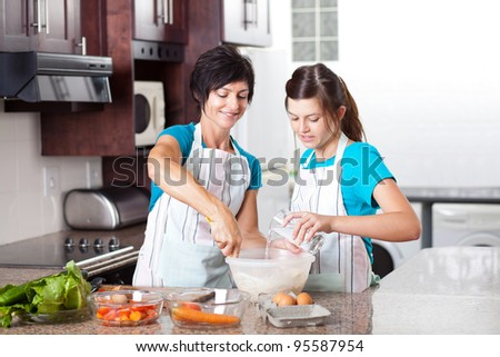 teen daughter helping mother baking in kitchen - stock photo