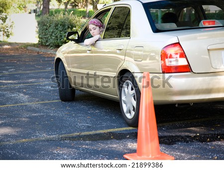 Teen driver backs up, doing the parking portion of her driving test. - stock photo