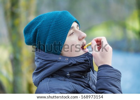 Teen eating french fries in the park - stock photo