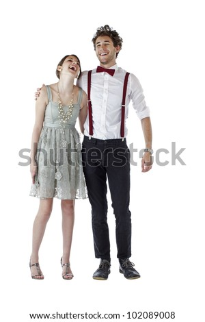 Teen girl and boy dressed formally for a prom hug each other and laugh. Vertical, isolated on white, copy space.