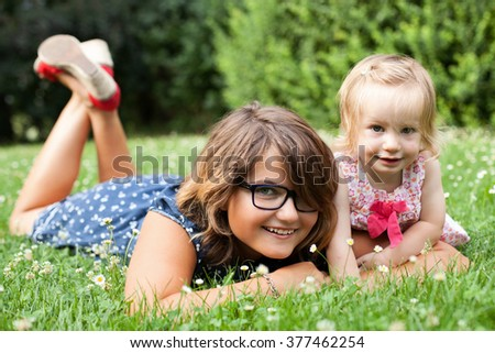 Teen girl and her toddler sister on the grass - stock photo