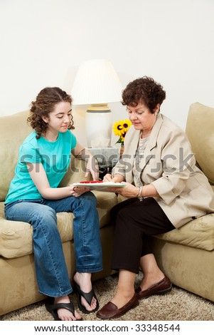 Teen girl and older woman filling out paperwork during an interview. Could be counseling session or job application.  Vertical with copyspace. - stock photo