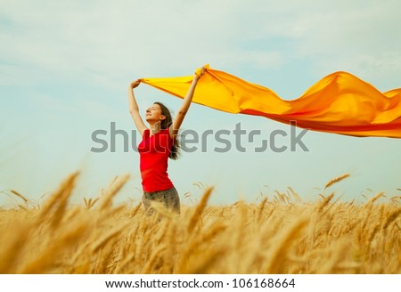 Teen girl at a wheat field with yellow fabric - stock photo