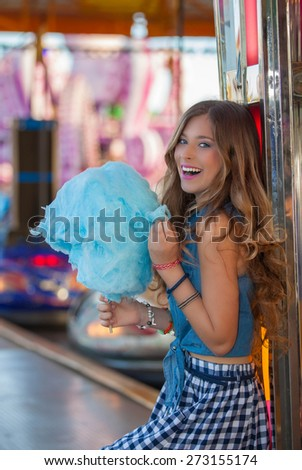 teen girl at carnival or fair with candy floss or cotton candy   - stock photo