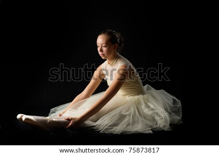 teen girl ballet dancer sitting in a tutu in points on a black background stretching - stock photo
