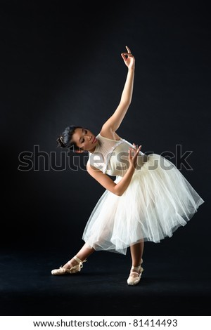 teen girl ballet dancer standing in a tutu in points on a black background