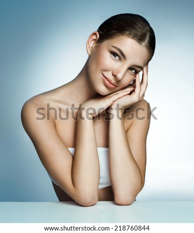 Teen girl beautiful cheerful enjoying with clean skin. Woman skin care concept / photos of amazing Latina girl on blue background  - stock photo