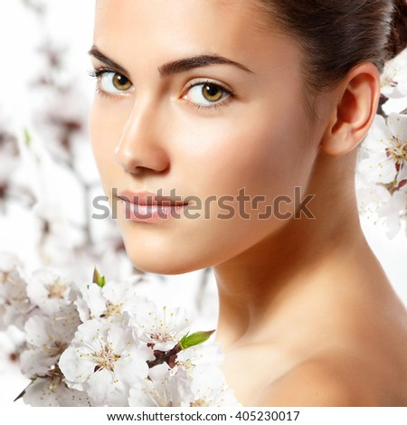 teen girl beauty portrait looking at camera over blooming tree with flowers. Spring, youth, freshness, beauty, skincare and health-care concept.