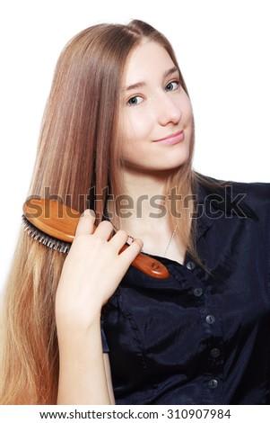 teen girl brushing her hair on white background - stock photo