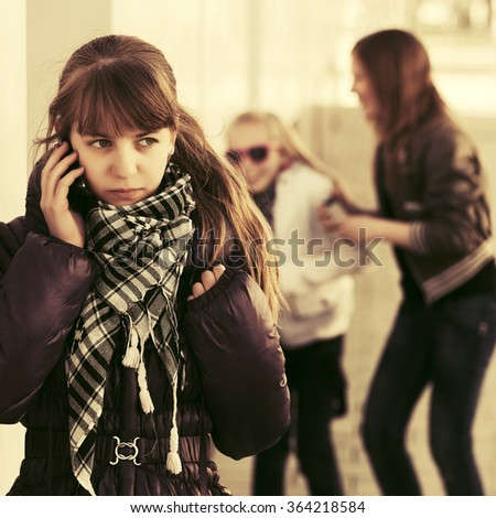 Teen girl calling on cell phone at the wall - stock photo