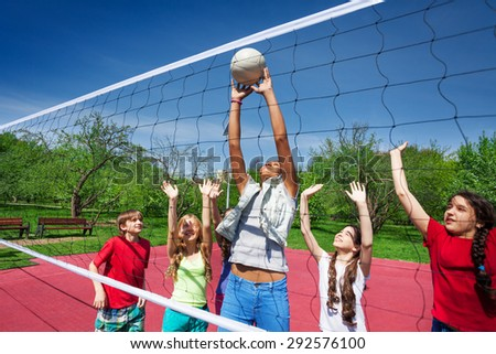 Teen girl catches the ball during volleyball game - stock photo