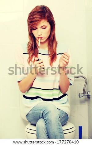 Teen girl caught on smoking in bathroom - stock photo