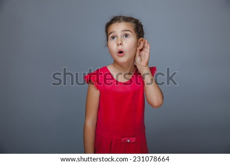 Teen girl child listens hand at the ear on gray background - stock photo