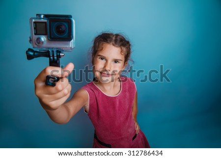 Teen girl child seven years, European appearance brunette holding action camera and smiling on a gray background, shot, joy - stock photo