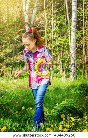 Teen girl collects flowers dandelions on a green meadow