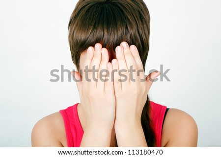 teen girl covers her face with both hands - stock photo