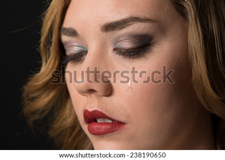 Teen girl crying, with a tear drop running down her cheek.   - stock photo