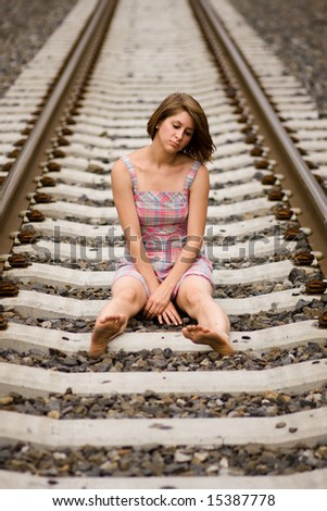 Teen girl depressed on railroad track - stock photo
