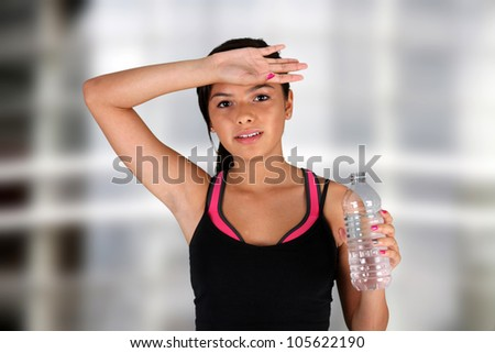 Teen girl drinking water at the gym - stock photo