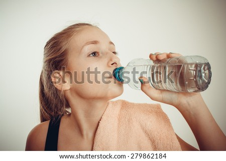 Teen girl drinks bottled water after exercising, vignette toned - stock photo