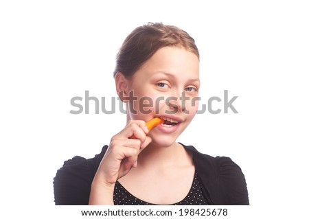 Teen girl eating carrot, studio shot