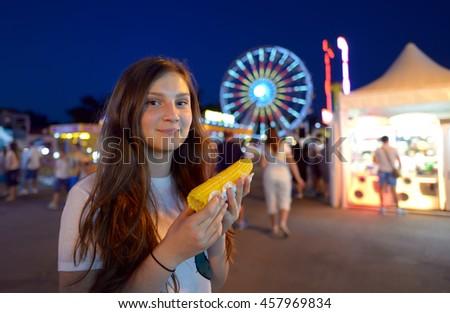 teen girl eating corn in fair - stock photo
