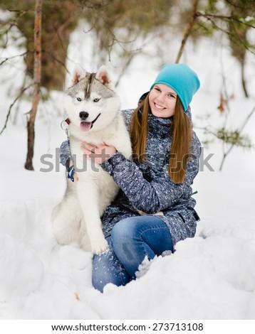 Teen girl embracing hasky dog in winter park - stock photo