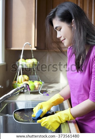 Teen girl happily washing dishes at kitchen sink - stock photo