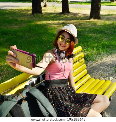Teen girl has fun outdoor and make photos with smartphone. - stock photo