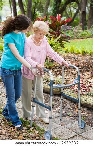 Teen girl helping her grandmother cope with a walker. - stock photo