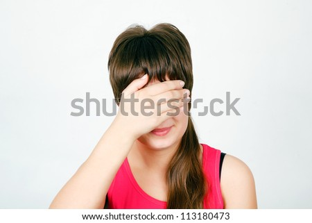 Teen girl hides her face in his hand
