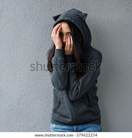 Teen girl hides her face quizzically - stock photo