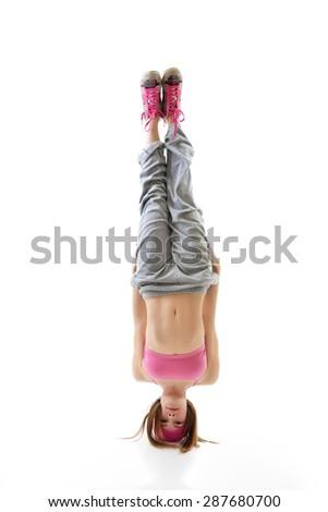 Teen girl hip-hop dancer standing on head over white background - stock photo