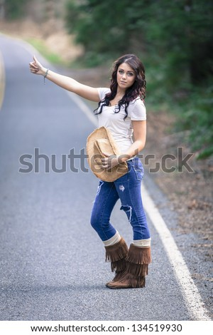 Teen girl hitchhiking with cowboy hat - stock photo