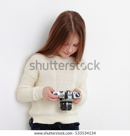 Teen girl holding photo camera and taking pictures