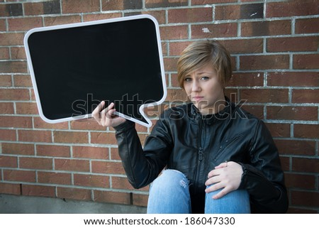 Teen girl holds up sign with brick wall background, with copy space for your text - stock photo