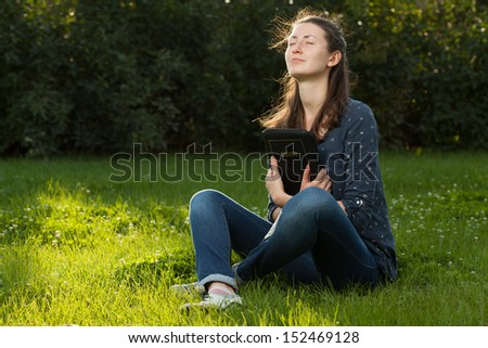 Teen girl hugging the Bible sitting outdoors with copy space - stock photo
