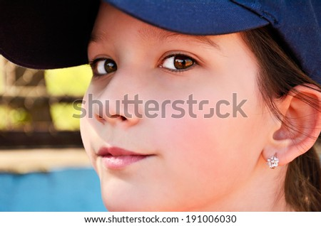 teen girl in a cap looking at the camera. closeup, horizontal, side view - stock photo