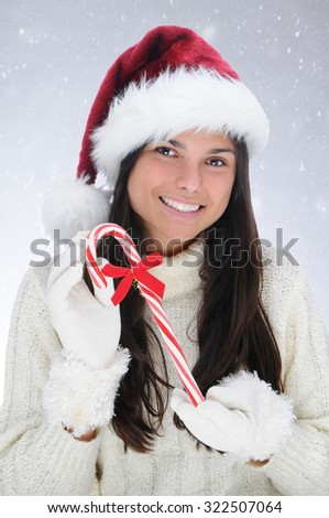 Teen girl in a Santa Claus hat holding Christmas candy cane. Horizontal format with snowy background.