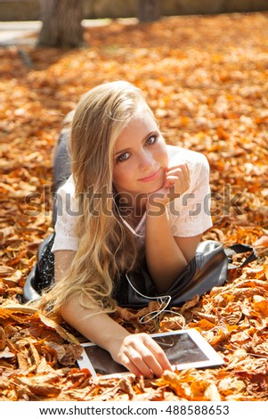 Teen girl in autumn park with pc