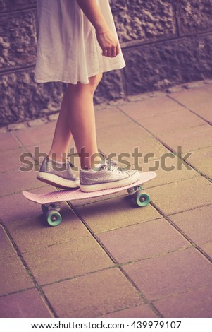 teen girl in dress and sneakers on skate outdoor summer day at street closeup