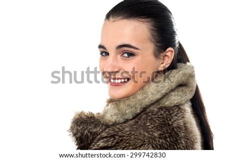Teen girl in fur jacket, looking over shoulder - stock photo