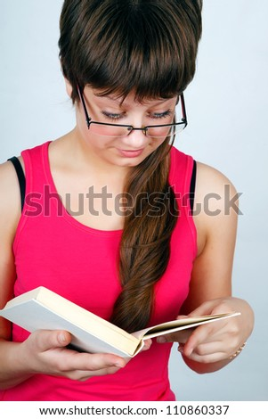 Teen girl in glasses reads the book carefully