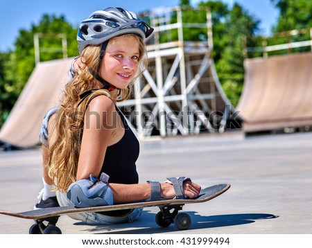 Teen girl in helmet sitting on his skateboard outdoor. Childhood with skateboarding .