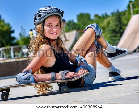 Teen girl in helmet sitting on his skateboard outdoor. Fall on person . Successful landing.
